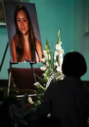 A mourner pauses in front of a picture of Ashton Sweet during a memorial service at the Chinese Baptist Church of Central Orange County in Irvine.