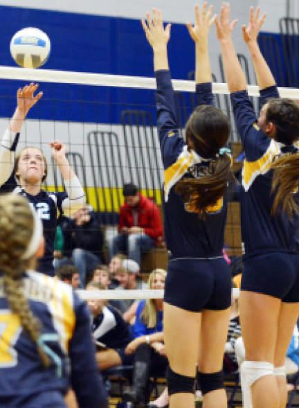 Petoskey senior outside hitter Kati Lewis (left) attacks the ball as Gaylords Casey Korte (middle) and Dakota Pelach attempt the block during Mondays Big North Conference match at the Gaylord High School gym. The Northmen fell to the Blue Devils in three sets, 25-19, 25-19, 25-23.
