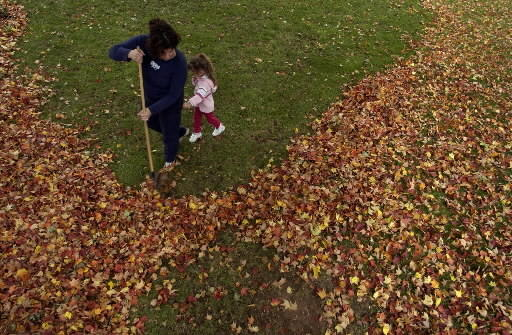 Susan Nasby and daughter Lauren Nasby, 3, rake leaves at their West Hartford home in 2003
