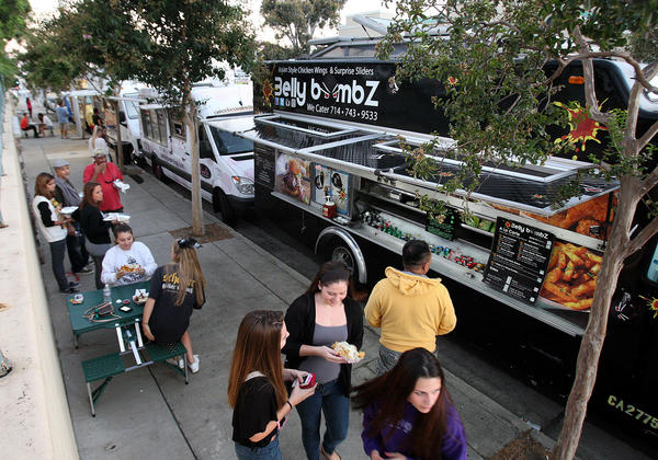 People, either waiting for their food or sitting on portable picnic tables in front of Ralphs in La Crescenta where food trucks gather for a weekly Food Truck Fundraiser for Crescenta Valley High School on Thursday, September 26, 2013.