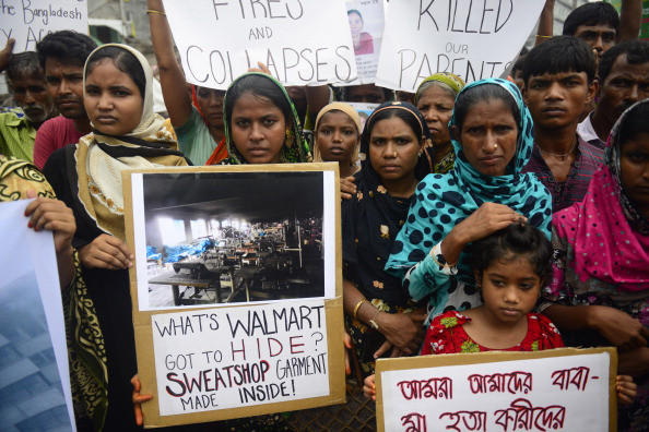 Relatives of Bangladeshi workers who lost their lives in a garment factory disaster gather with banners and placards in Savar, on the outskirts of Dhaka on June 29, 2013,