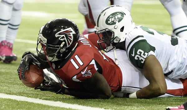 Jets safety Josh Bush stops Falcons wide receiver Julio Jones from getting into the end zone during the first half of their game Monday.