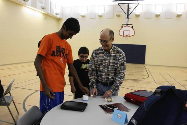 Glenview resident John MacDougall, right, demonstrates properties of magnets to Vince Abraham, 13, left, and other students during a tutoring session as part of the Study Buddies program at Youth Services of Glenview/ Northbrook on Monday night, Oct. 7.