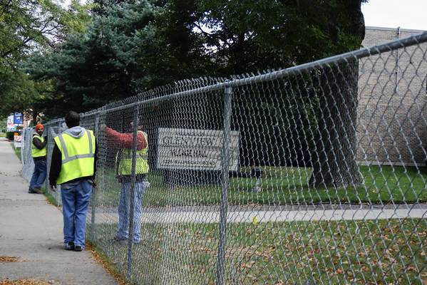 Workers put up a fence around a construction site on Monday, Oct. 7, near the Glenview Village Hall where demolition is scheduled to start soon. Officials hope to complete the new Glenview Fire Department headquarters in 2014.