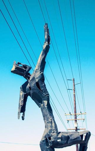 One of artist Louis Longi's sculptures seemingly reaches for the power to turn his property into a new live-work complex with 30 units on Laguna Canyon Road.