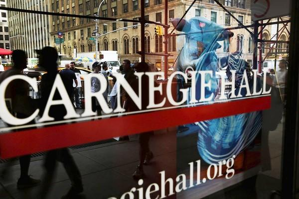 Members of Local 1 International Alliance of Theatrical Stage Employees are reflected in a window as they picket outside of Carnegie Hall.