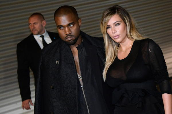 Rapper Kanye West (left) and his wife and reality TV star Kim Kardashian (right) pose prior to Givenchy 2014 Spring/Summer ready-to-wear collection fashion show Sept. 29, 2013 in Paris.
