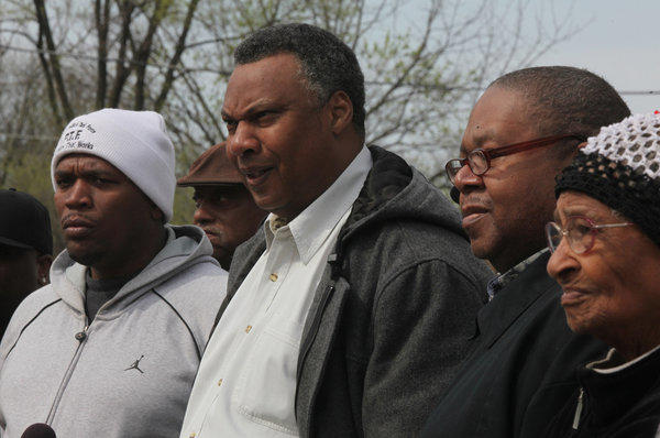 Community Activist Hal Baskin, center, stands outside Sheree's tavern, Tuesday, March 27, 2012, along with other community activists and residents, where owner Homer Wright, 80, shot an intruder.
