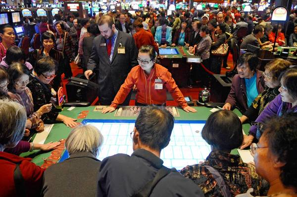 Dealer Xian Yang runs a Sic Bo table that is crowed with Asian gamblers on Monday afternoon.