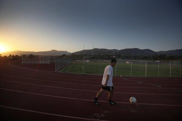 Kenan Jiang, 22, of Malibu, kicks a soccer ball while running at the Malibu High School track. Some classrooms inside a building on the adjacent middle school campus are being relocated because of concerns over possible toxins.