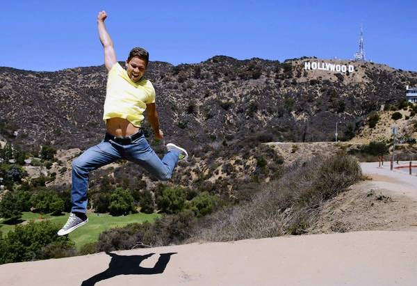 """Waldemar Scott jumps in front of the Hollywood sign last month as a friend snaps his picture near Canyon Lake Drive in the Hollywood Hills. The rising number of tourists has """"really gotten out of hand,"""" one nearby resident says."""
