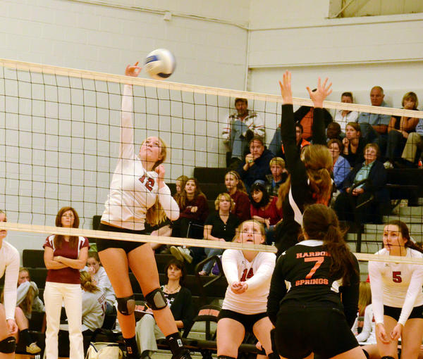 Charlevoix senior Hannah Zipp (left) spikes the ball as teammate Jennaca Holecheck (middle) covers against Harbor Springs during a Lake Michigan Conference match at the Harbor Springs High School gym on Tuesday. The Rayders defeated the Rams, 25-14, 25-19, 25-19.
