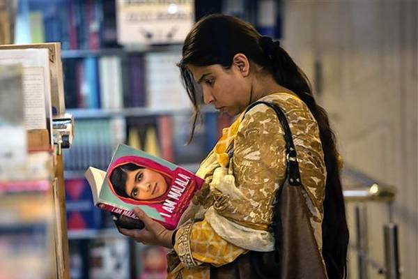 "A woman browses a copy of Malala Yousufzai's book ""I am Malala"" at a book store in Islamabad."