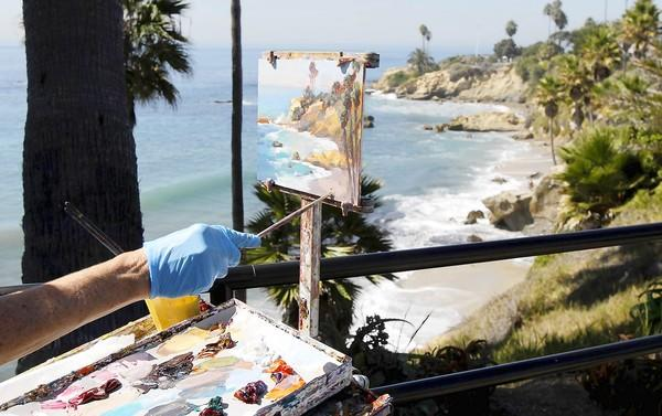 The steady hand of artist Kathleen Robison paints the beach at Rockpile as she participates in the 2012 Laguna Beach Plein Air Painting Invitational.
