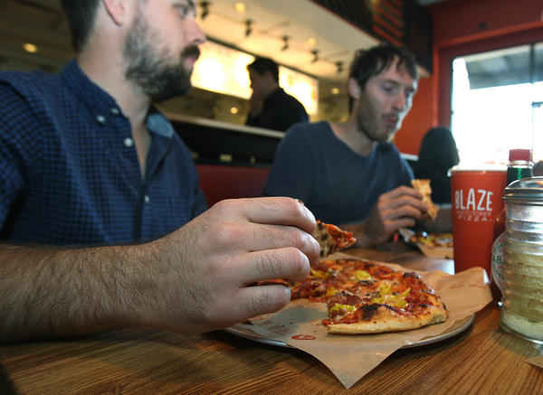Max Baybak, of La Cañada, Zach Schrock, who works in Montrose, and Matt Johnson, of La Cañada, eat at Blaze Pizza in La Cañada Flintridge, a new restaurant that serves a fresh custom made gourmet pizza in 120 seconds on Tuesday, Oct. 8, 2013.