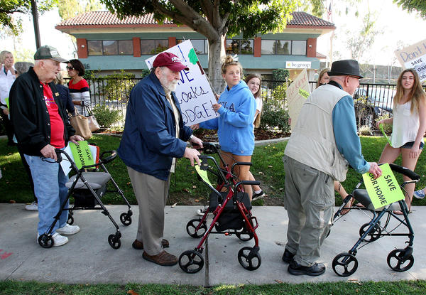 12 Oaks Lodge residents Bill Hughes, 93, John Meilan, 90, and Jim Davidson, 91, with the be.group building in the background, march in front of the business in Glendale, protesting the closing of their La Crescenta residence on Wednesday, Oct. 2, 2013.