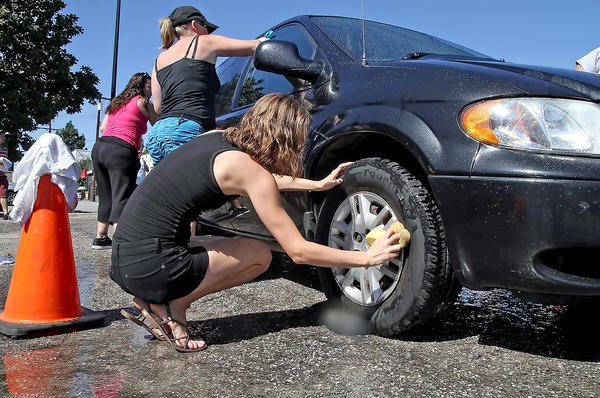Britini Parish scrubs the tire of a car during a car wash fundraiser on Saturday, Oct. 5, 2013 at Foster Freeze on Glenoaks Boulevard. Donations were collected for the families of five car crash victims.