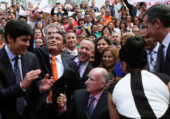 Jubilant lawmakers surround California Gov. Jerry Brown as he signs legislation to grant drivers' licenses to immigrants in the county illegally.
