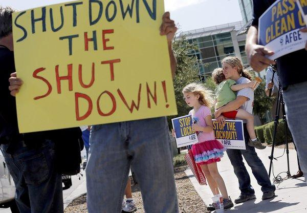 As the federal government shutdown continues, Tory Anderson, right, with her kids Audrey, 7, and Kai, 3, of Goodyear, Ariz., join others as they rally in front of the Social Security Administration offices in Phoenix.