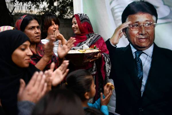 Supporters of former Pakistani President Pervez Musharraf, in poster, celebrate at a gathering in Islamabad after a court decision to grant him bail.