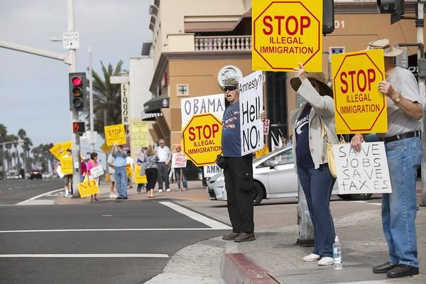 Dan Russell, from San Diego, center, shouts at passing motorists during an anti-immigration protest on the corner of Pacific Coast Highway and Main Street in Huntington Beach on Tuesday.
