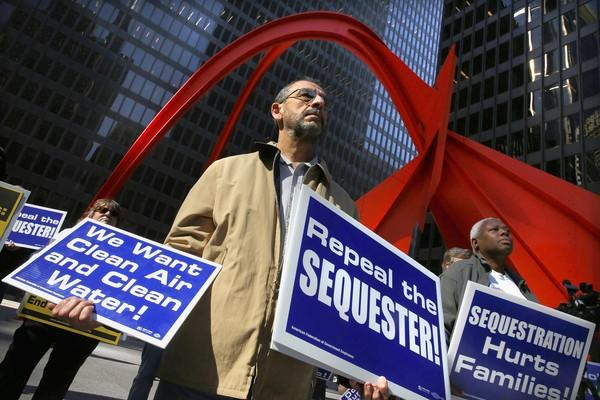Simon Manoyan, center, an Environmental Protection Agency scientist, rallies with co-workers and other furloughed federal employees and supporters Wednesday outside the Kluczynski Federal Building in Chicago.