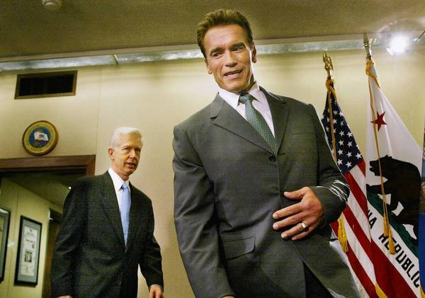 Then-Gov.-elect Arnold Schwarzenegger, right, walks into the conference room in the governor's office, with then-California Gov.Gray Davis, left, after the two met privately on Oct. 23, 2003. The recall that had just been held replaced career politician Davis with Hollywood action hero Schwarzenegger.