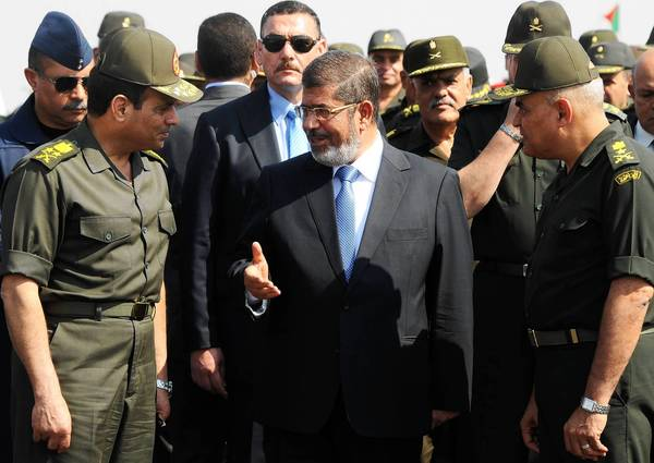 Then-President Mohamed Morsi talks with Defense Minister Gen. Abdel Fattah Sisi, left, at a military base in Ismailia, Egypt, in October 2012. The U.S. says it will maintain key assistance for security and counter-terrorism efforts in Egypt but suspend delivery of tanks, helicopters and other new military hardware in response to the military ouster of Morsi in July.