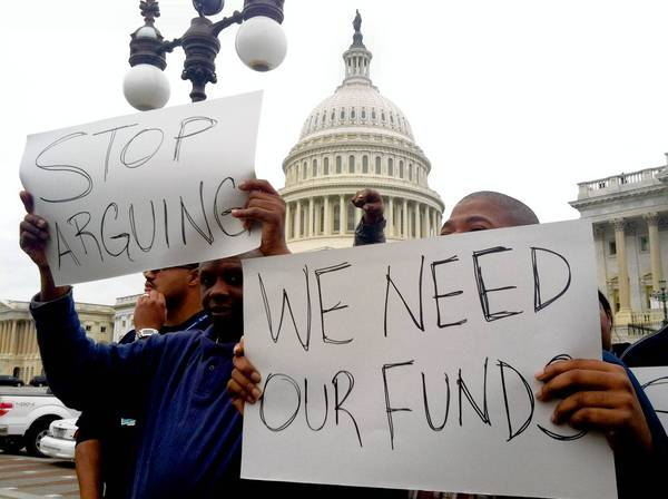 Protesters urge Congress to end the federal shutdown. A default could spur the Fed to take steps to increase liquidity.