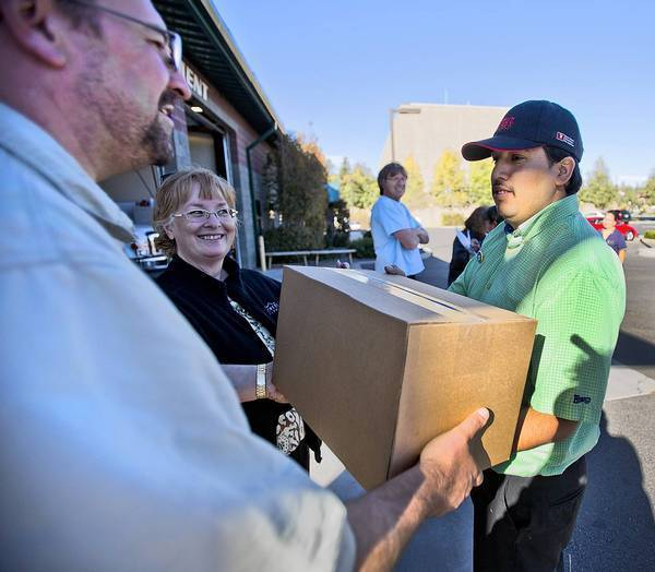 Volunteer David Cole, left, hands Richard Contreras a box of donated food Tuesday in Tusayan, Ariz. The government shutdown has left workers at the Grand Canyon stranded without pay or food.