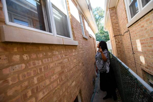 The sister of a sexual assault victim looks at the kitchen window in a gangway at her sister's house in the 10300 block of South Emerald Avenue in Chicago. A man entered the house through the window early Wednesday and allegedly sexually assaulted the victim and her grown daughter.
