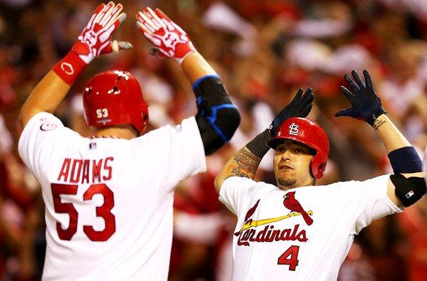 Cardinals catcher Yadier Molina (4) congratulates first baseman Matt Adams after he hit a two-run home run in the eighth inning of Game 5 in the National League division series against the Pittsburgh Pirates on Wednesday night at Busch Stadium in St Louis.