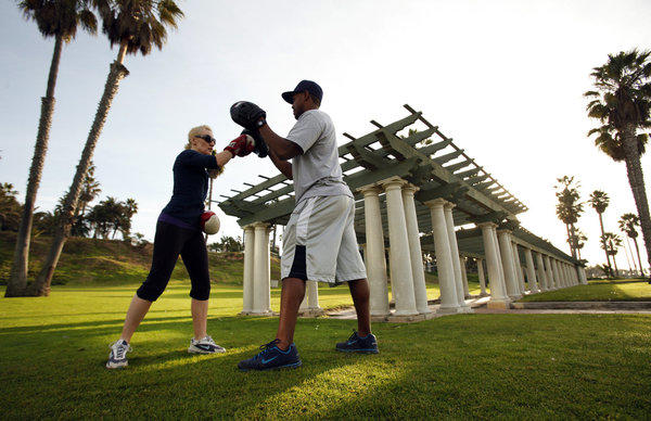 Ruben Lawrence, right, trains Ali Janes during a boxing class at Crescent Bay Park in Santa Monica.