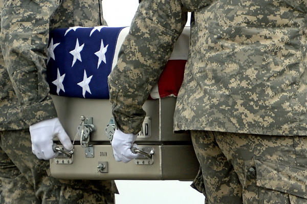 Army soldiers carry the flag-draped transfer case containing the remains of U.S. Army Pfc. Cody J. Patterson during a dignified transfer at Dover Air Force Base.