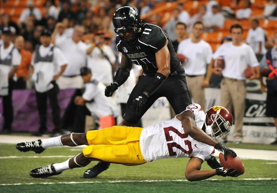 Trojans running back Justin Davis dives into the end zone before Hawaii's Tavita Woodard can stop him from scoring in the fourth quarter Thursday night at Aloha Stadium in Honolulu.
