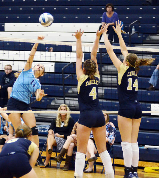 Petoskey junior Sara Donakowski (left) goes up for an attack as Cadillac senior Selena Golnick (4) and freshman Kylie Christensen (right) attempt the block during Wednesdays Big North Conference match at the Petoskey High School gym. The Northmen fell to the Vikings in three sets, 25-10, 25-19, 25-17.