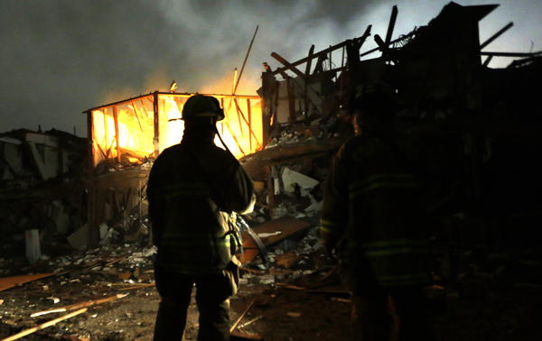 Firefighters search a destroyed apartment complex near the fertilizer plant that exploded in West, Texas, in April. OSHA has cited the plant's owner for 24 safety violations, including the unsafe handling and storage of chemicals, and has proposed $118,300 in penalties.