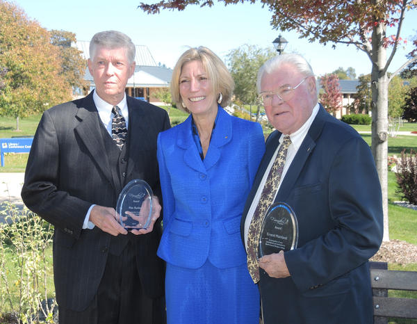 Max Bunker (left) and Ernest F. Mainland (right) are congratulated by North Central Michigan College President Cameron Brunet-Koch (center). The two men were honored at the NCMC Founders Society Luncheon on Tuesday, Oct. 8, for their years of volunteer service and charitable giving to the university.