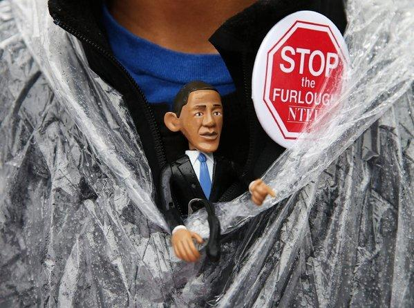 A protester wears an Obama figure during a rally outside the U.S. Capitol in Washington to urge an end to the government shutdown.
