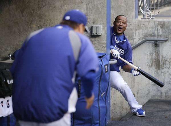 Juan Uribe jokingly bunts off of Hyun-Jin Ryu during practice at Dodger Stadium on Wednesday for Game 1 of the NLCS.