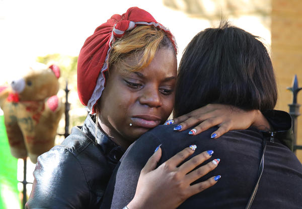 Coco Coolei, left, comforts a friend as they and others mourn the three victims of a triple murder in the 6700 block of south Chappel.
