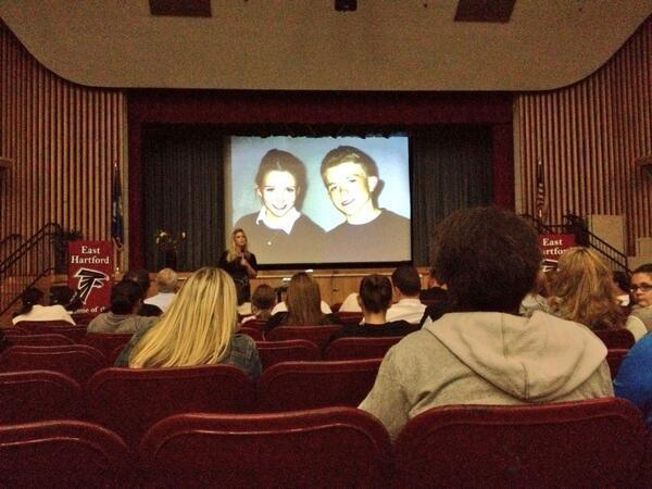 Presenter DeeDee Cooper shows a photo of Rachel Joy Scott, left, with her younger brother Craig. Scott was the first person shot and killed at Columbine High School in 1999 and Craig, who was also a student there, played dead in the library before helping lead others to safety.