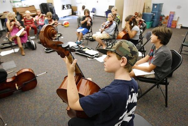 Wyatt Beckley gently plucks the strings on a cello as he tries to learn a simple song during a fourth-grade orchestra class at Top of the World Elementary School on Tuesday.