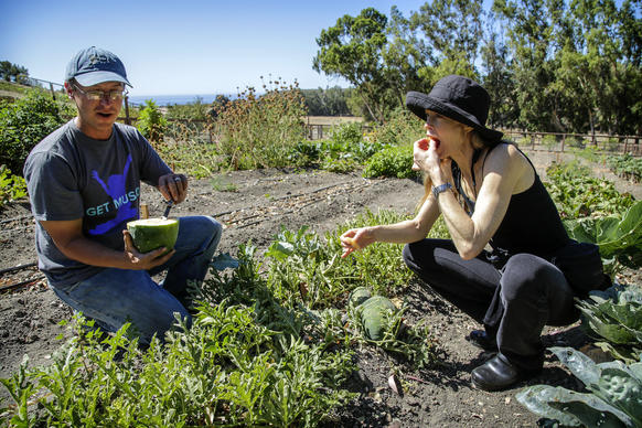 Garden consultant Paul Hudak and Suzy Amis Cameron sample a Moon and Stars watermelon in one of the mini farm's gardens overlooking the Pacific Ocean in the Santa Barbara area.