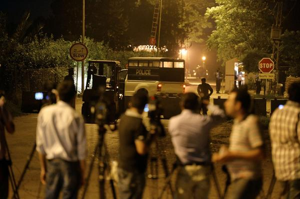 Police stand guard and journalists gather outside the residence of former Pakistani President Pervez Musharraf in Islamabad, the capital.