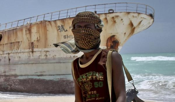 Masked Somali pirate Abdi Ali stands near a Taiwanese fishing vessel that washed up on shore after the pirates were paid a ransom and released the crew in Hobyo, Somalia.