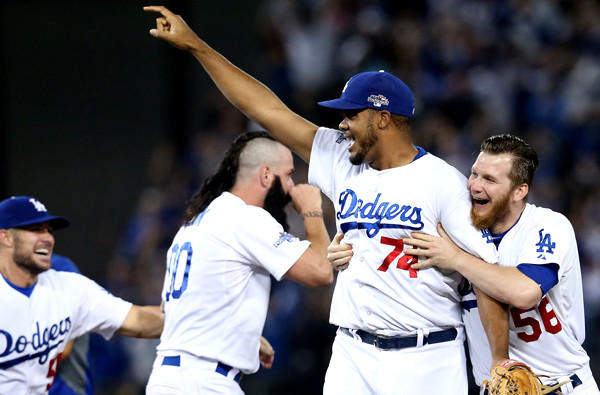Dodgers closer Kenley Jansen (74) is swarmed by relievers Brian Wilson (00) and J.P. Howell (56) after defeating the Atlanta Braves, 4-3, in Game 4 of the NL division series.