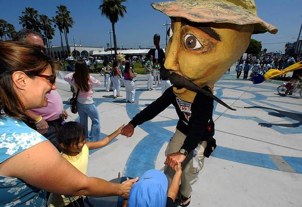 A participant in Venice's centennial celebration in 2005 greets visitors while wearing a mask representing Abbot Kinney, founder of the beachside community. Abbot Kinney Boulevard is a model of what L.A. Mayor Eric Garcetti wants to see in other neighborhoods.