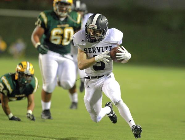 Servite running back Nick Lopiccola breaks past Edison High defenders during Anaheim's 31-14 victory on Sept. 19, 2013.