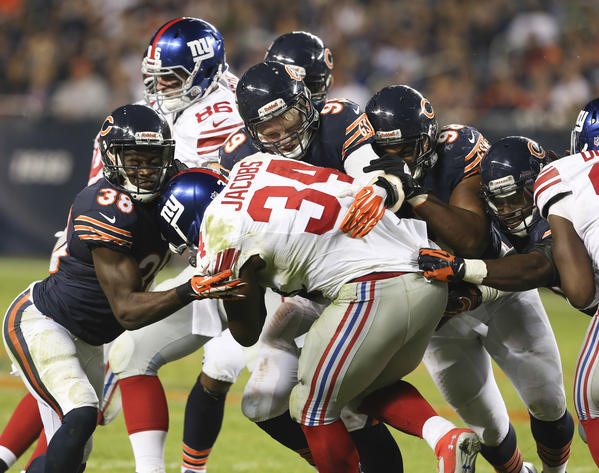 Giants running back Brandon Jacobs is brought down by Bears defenders during the second half.